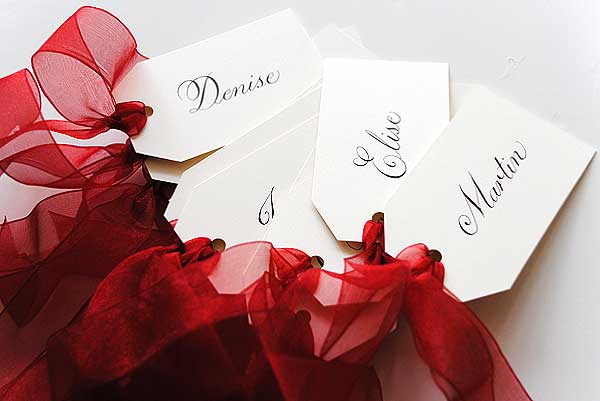 These luggage tags were handwritten for a wedding with a sheer red ribbon